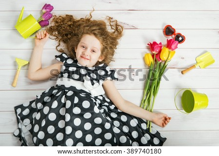 Curly girl with bouquet of tulips lying on white wooden floor. Spring background, Birthday party, Easter day, Valentine day concept.