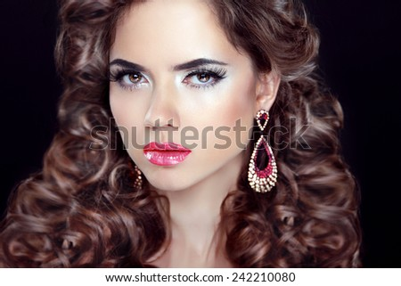 Curly hair. Beautiful girl model portrait with fashion earring over dark background. Beauty makeup. Hairstyle.