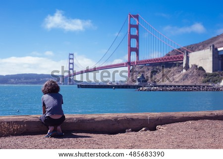 Curly hair boy sitting by the shore of the bay looking out to Golden Gate Bridge the iconic landmark of San Francisco with blue sky and green water bay background with toned color and selective focus