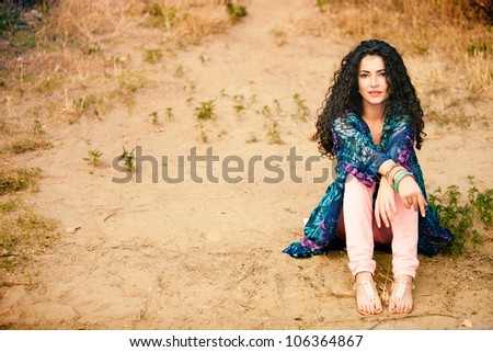 curly hair smiling woman in colorful dress sit on ground full body shot outdoor summer day