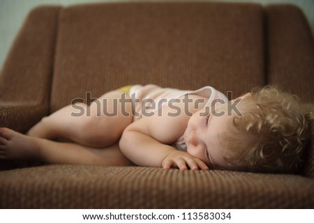 Curly haired blonde baby girl sleeping on armchair