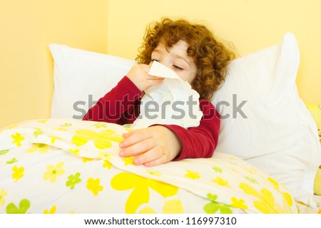 Curly haired little sick girl laying in bed and blowing her nose. - stock photo