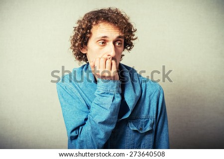 curly-haired man bites his nails - stock photo