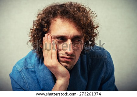 curly-haired man leaned his chin on hand