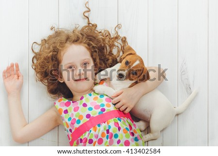 Curly little girl with her puppy Jack russell terrier lying on a wooden floor. - stock photo