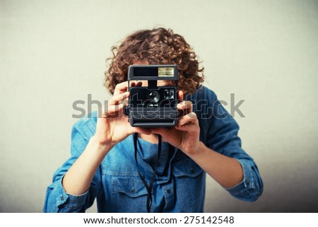 Curly man with a camera snapshots. On a gray background. - stock photo