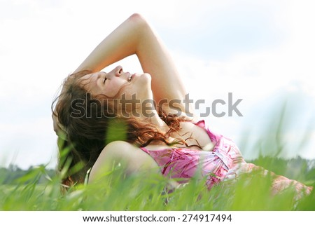 Curly redhead Girl dream on fresh spring green grass meadow with closed eyes Cute caucasian young adult woman lie in spring field against blue sky with clouds and forest Alone Female enjoy summer day  - stock photo