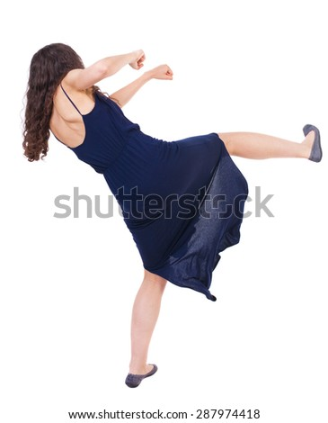 curly woman funny fights waving his arms and legs. Isolated over white background. Girl in a blue evening dress fights feet. - stock photo