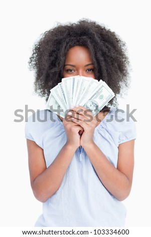 Curly woman hiding her face behind a fan of dollars against a white background