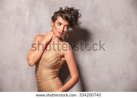 curly woman in sexy dress pose arching her back while touching her neck