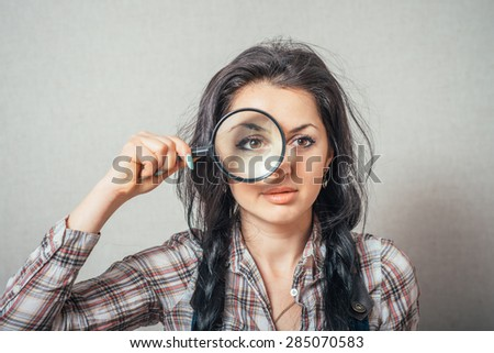 Curly woman looking through a magnifying glass. On a gray background.