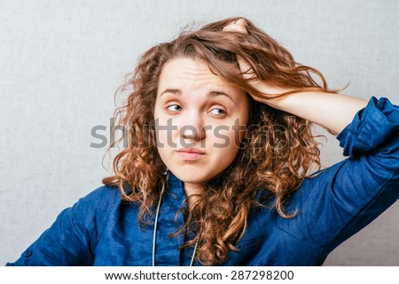 Curly woman scratching her head. Gray background. - stock photo