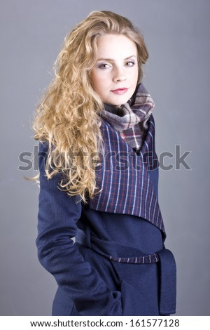 curly young blond woman in a stylish blue coat on gray background