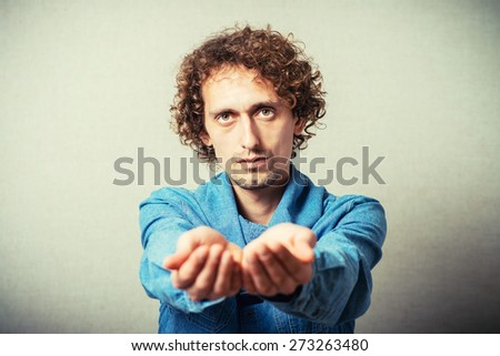 Curly young man showing empty palm. On a gray background - stock photo