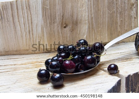 Currant.  on spoon and wooden background. - stock photo