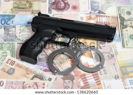 Currency from world with handcuffs and handgun - stock photo
