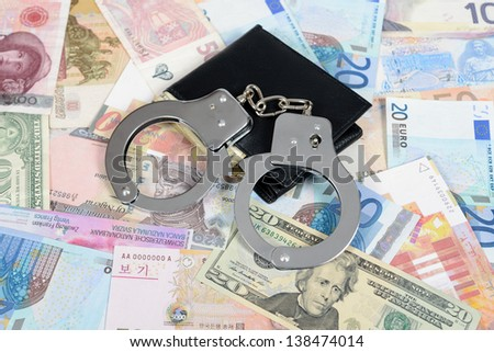 Currency from world with handcuffs and wallet - stock photo