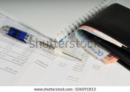 Currency in wallet and pen on sheets of banking report