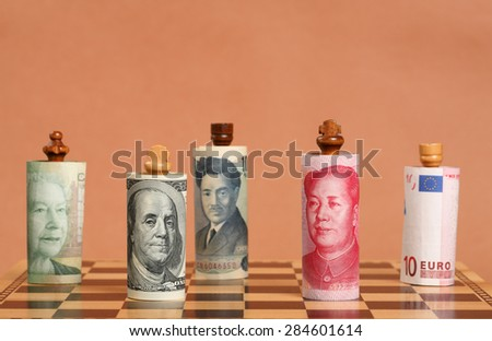 Currency War. Chess Dressed in Different Banknotes on a Chess Board. - stock photo