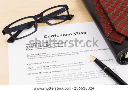 Curriculum vitae with pen, glasses, organizer, and neck tie; CV is mock-up - stock photo