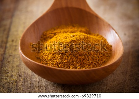 Curry in a wooden spoon - stock photo