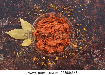 Curry paste in glass bowl with various spices on brown rustic background - stock photo