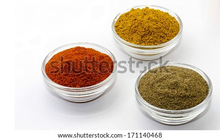 curry pepper and paprika in glass bowls isolated - stock photo