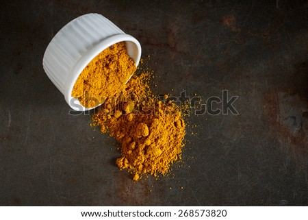 curry powder in small white cup image soft focus , put on grunge metal background - stock photo