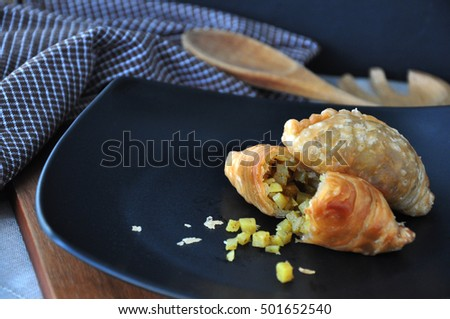 Curry puff with stuff on black plate