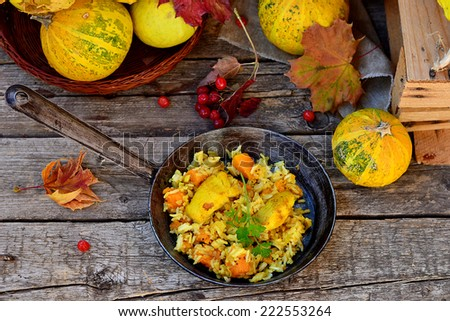 curry rice with pumpkin and fish on an autumn background with pumpkins and fallen leaves.selective focus - stock photo
