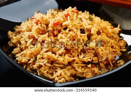 Curry rice  with vegetables on black square dish, chopsticks, dark wood table - stock photo