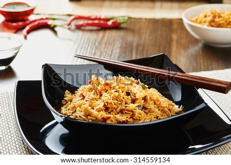 Curry rice with vegetables on black square dish, chopsticks, soy sauce, dark wood table and ingredients - stock photo
