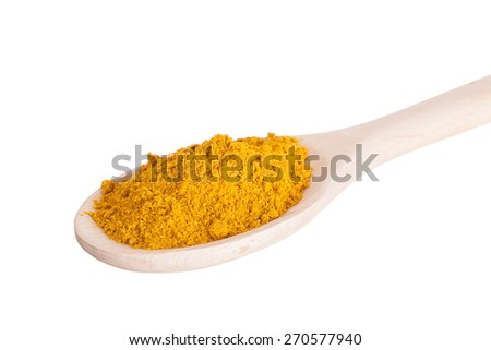 Curry seasoning in a wooden spoon, it is isolated - stock photo