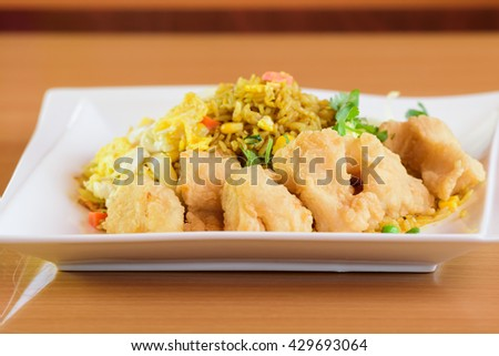 Curry yellow rice with herbs on plate over white background