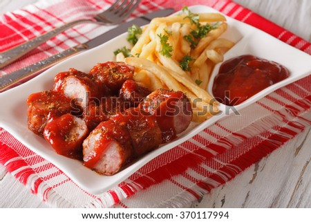 Currywurst sausage with french fries close-up on a plate. Horizontal - stock photo