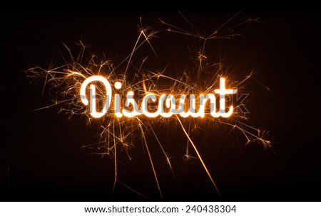 Cursive DISCOUNT sign in sparkly design on black background. - stock photo