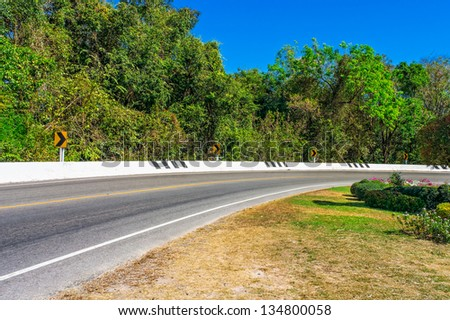 Curve asphalt road with edge barrier is the one part of transportation industrial system - stock photo