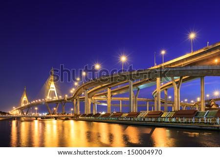 Curve of expressway by river in Bangkok at night - stock photo