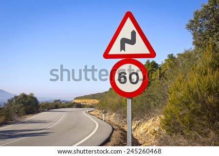 Curve on mountain road with a right reverse band traffic sign and a speed sign of 60 kilometers per hour. Was seen in the Extremadura, Spain. - stock photo