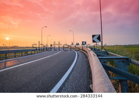 curve on the road at the sunset - stock photo
