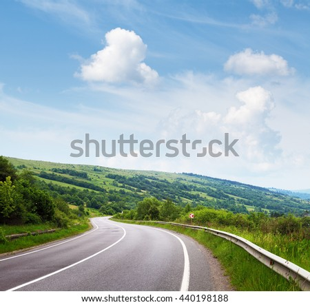 Curve road and blue sky over green hills. Summer landscape