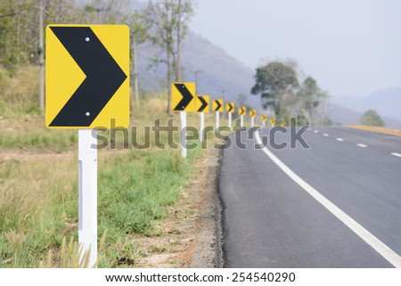 Curve warning sign on the road - stock photo