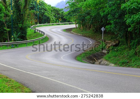 Curve way of asphalt road in the green view. - stock photo