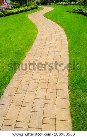 Curved and paved path, sidewalk with nicely trimmed grass aside