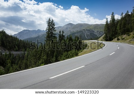 Curved asphalt on mountain road - stock photo