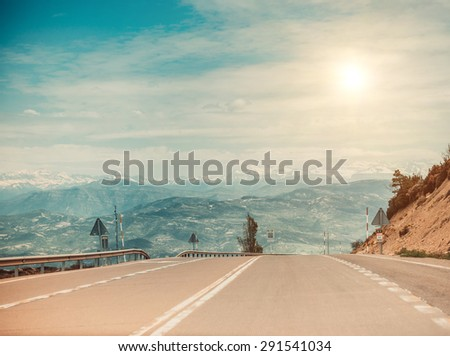 Curved asphalt road in high mountains - stock photo