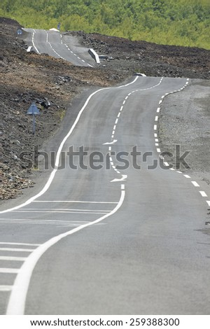 Curved asphalt road over volcanic lava, Reunion island, France. - stock photo