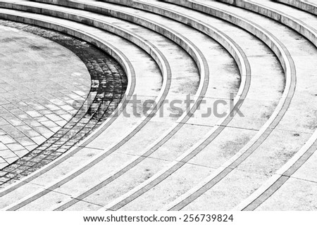 Curved concrete steps as an abstract image in black and white - stock photo