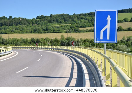 Curved feeder road in countryside, white arrow traffic sign in foreground   - stock photo