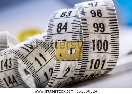 Curved measuring tape. Measuring tape of the tailor. Closeup view of white measuring tape - stock photo